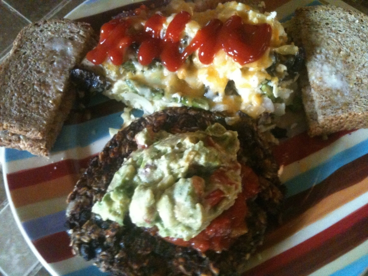 Mike's feast which was fit for a vegetarian king!  Crustless quiche with mushroom, asparagus, potato, caramelized onion and garlic, fresh basil, and cheese. Ezekiel bread and homemade black bean veggie burger patty topped with guacamole brimming with garden tomatoes and cilantro and salsa.