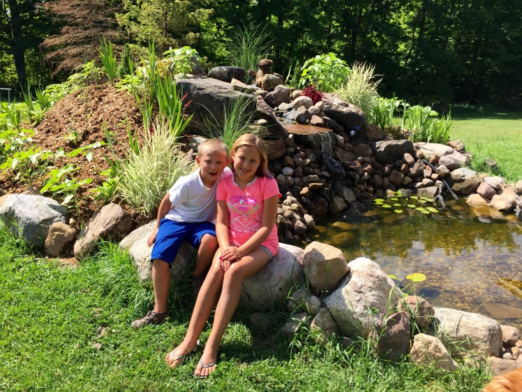 The beautiful pond John built and my adorable step kids.
